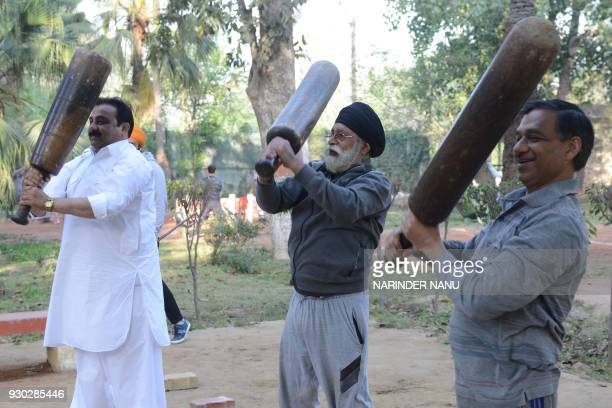 Indian people exercise by lifting traditional equipments in an outdoor gym in Amritsar on March 11 2018 / AFP PHOTO / NARINDER NANU