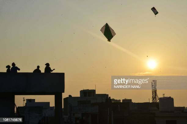 Indian people fly kites on the top of roofs during celebrations for the Lohri festival in Amritsar on January 13 2019 The Lohri harvest festival...