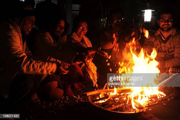 Indian people gather around a bonefire during the festival of Lohri in Amritsar January 13 2011 Lohri marks the culmination of winter and marks the...