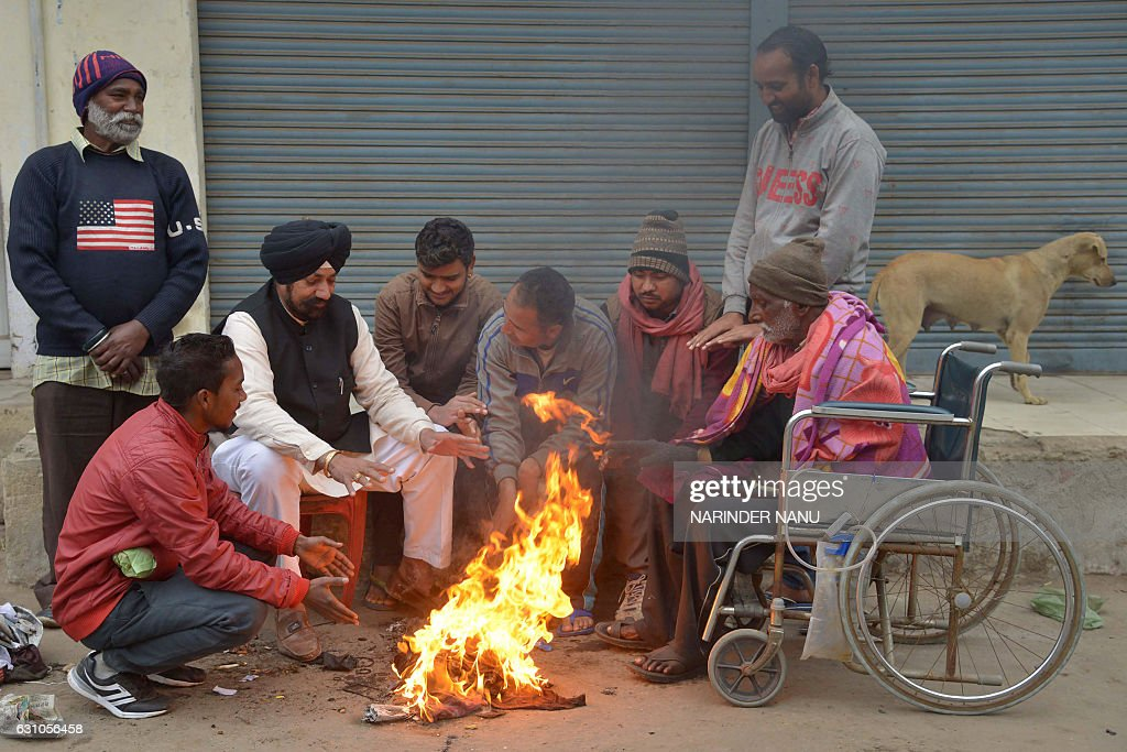 Indian people gather around a fire to keep warm on a cold day in Amritsar on January 6 2017 / AFP / Narinder NANU