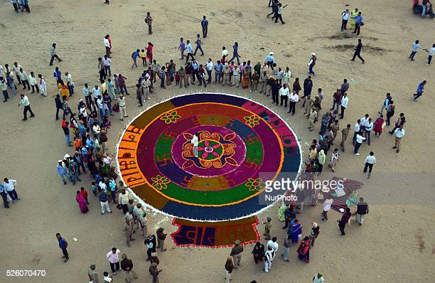 Indian people gather around a huge colorful Rangoli prepared by officials of Forest dept on the banks of Holy Sangam on the ocassion of Kartik...