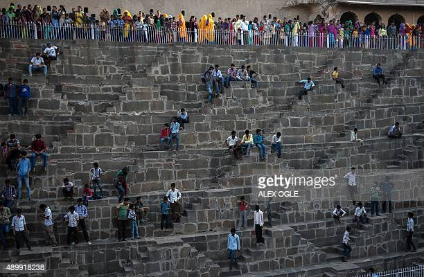 Indian people gather at the historic Chand Baori stepwell in Abhaneri village in Rajasthan on September 24 2015 For a few hours on one day each year...