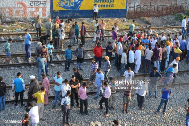 Indian people gather at the scene of an accident along railroad tracks in Amritsar on October 20 after revellers who gathered on the tracks were...