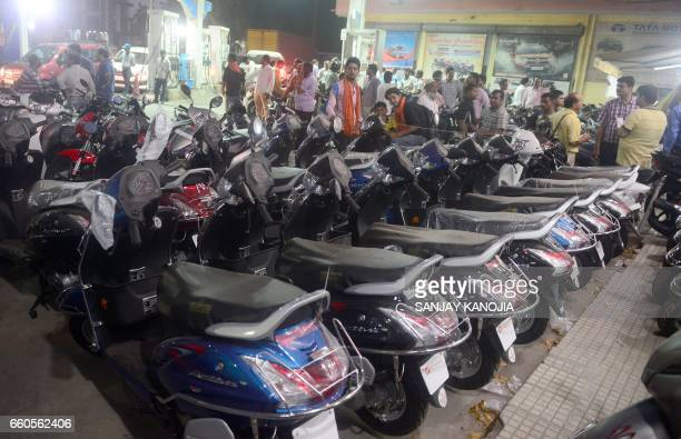Indian people gather outside an automobile showroom as companies dispose of BS3 emission standard vehicle at a heavy discount in Allahabad on March...