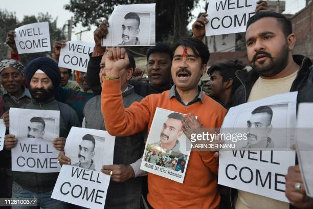 TOPSHOT Indian people hold placards and photographs of Indian Air Force pilot Abhinandan Varthaman as they celebrate the announcement of his soon...