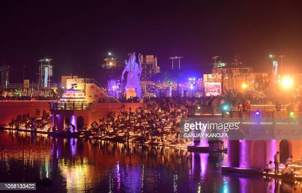 Indian people light earthen lamps on the banks of the River Sarayu on the eve of Diwali festival during a Deepotsav event organised by the Uttar...