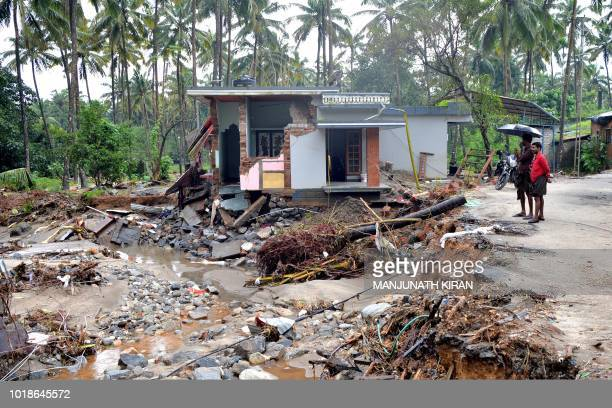 TOPSHOT Indian people look at a houses destroyed by a landslide at Kannapanakundu village about 422 km north of Trivandrum in the south Indian state...