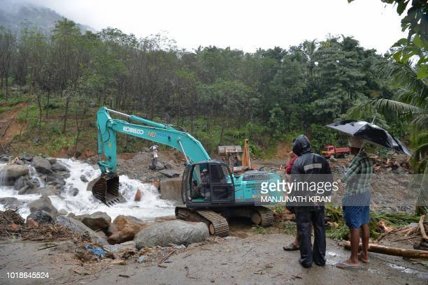 Indian people look at a loader machine removing boulders and blockage moved by a landslide at Mattikunnu village in Kozhikode district about 422 km...