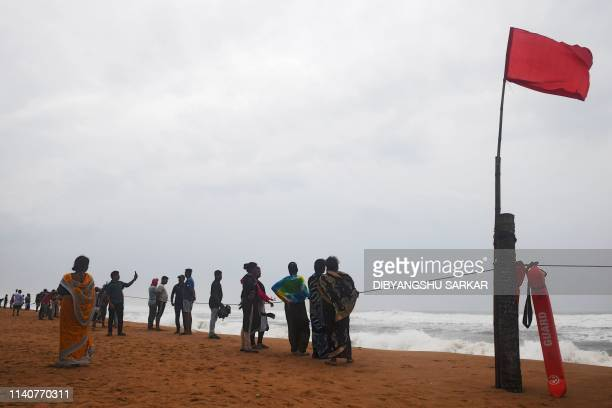 Indian people look out towards the sea from a closed beach in Puri in the eastern Indian state of Odisha on May 2 as cyclone Fani approaches the...