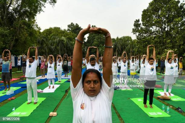 Indian people perform during a mass yoga session to mark International Yoga Day in Lodi Gardens in New Delhi on June 21 2018 Downwardfacing dogs...