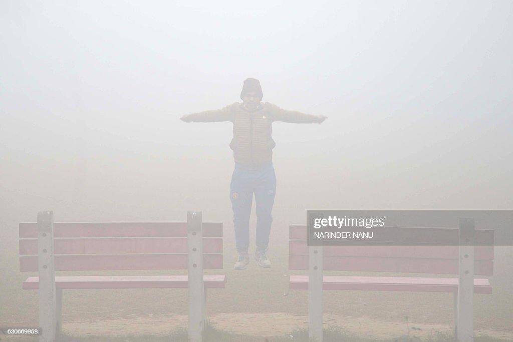 Indian people perform exercises during dense fog at a garden in Amritsar on December 30 2016 / AFP / Narinder NANU