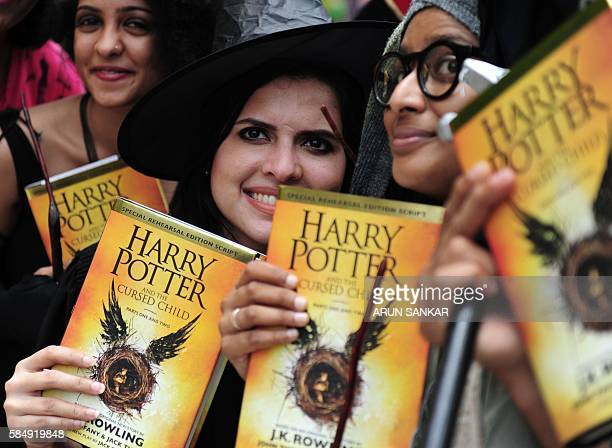 Indian people pose for phootgraphers with copies of JK Rowlings new book 'Harry Potter and the Cursed Child' during an event to mark the book launch...