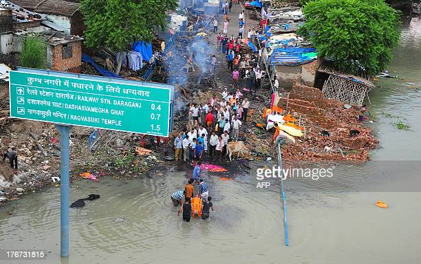 Indian people prepare funeral pyres on a flooded road as they carry a body for cremation at Daraganj Ghat as the river water level rises in Allahabad...