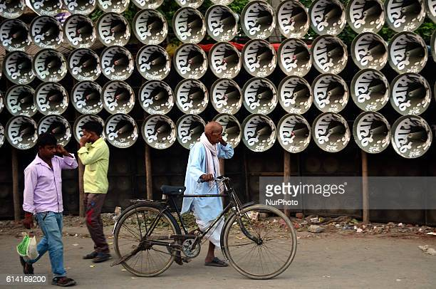 Indian people protect their ears as they walk next to loud music loudspeaker competition during a local fair in soraon villagesome 23 kms from...