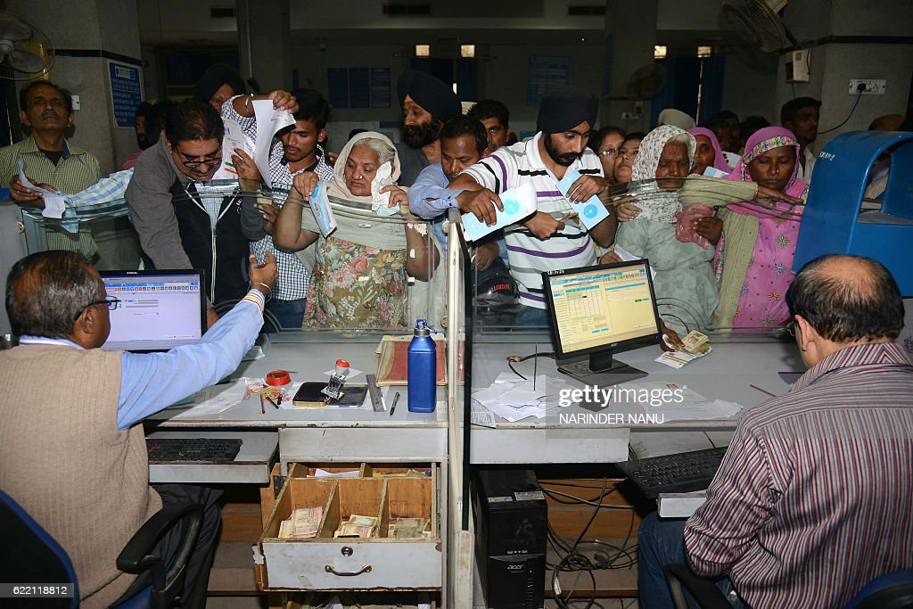 Indian people queue inside a bank to deposit and exchange 500 and 1000 Indian currency notes in Amritsar on November 10 2016 Long queues formed...