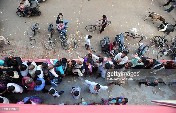 TOPSHOT Indian people queue outside a bank as they wait to deposit and exchange 500 and 1000 rupee notes in Allahabad on November 15 2016 India is to...