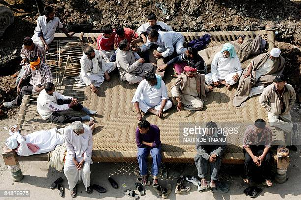 Indian people relax on a giant traditional rope bed in Amritsar on February 17 2009 The bed measuring some five meters by four meters was made by the...