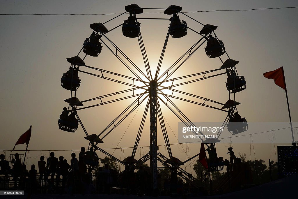 TOPSHOT Indian people sit on a ride at fair ground in Amritsar on October 11 2016 / AFP / NARINDER NANU