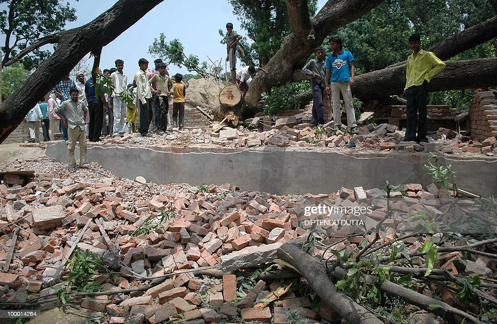 Indian people stand at the site of an uprooted tree and a collapsed buliding after a dust storm in Nababganj village, some 24 kms from Allahabad in Uttar Pradesh on May 20, 2010. At least nine persons, including two women and a young girl, were killed in the dust storm that hit the district's trans-Ganga region, the Press Trust of India reported. AFP PHOTO/Diptendu DUTTA