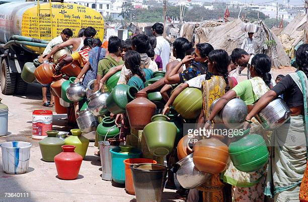 Indian people stand in a line as they wait to fill containers with drinking water supplied by a mobile water vehicle in a slum area in the Saidabad...