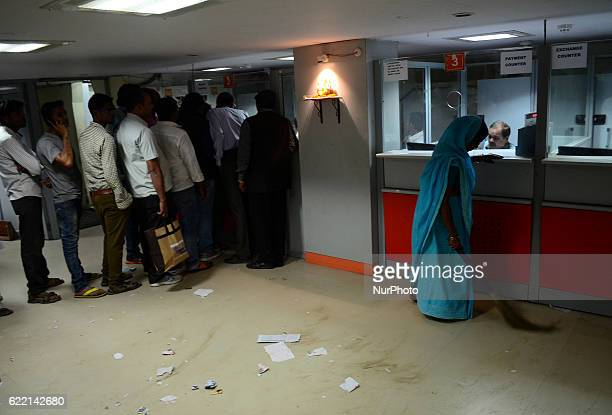 Indian people stand in a queue to deposit their money as a woman sweeper brooms the garbage in a bank , in Allahabad on November 10,2016..On the...