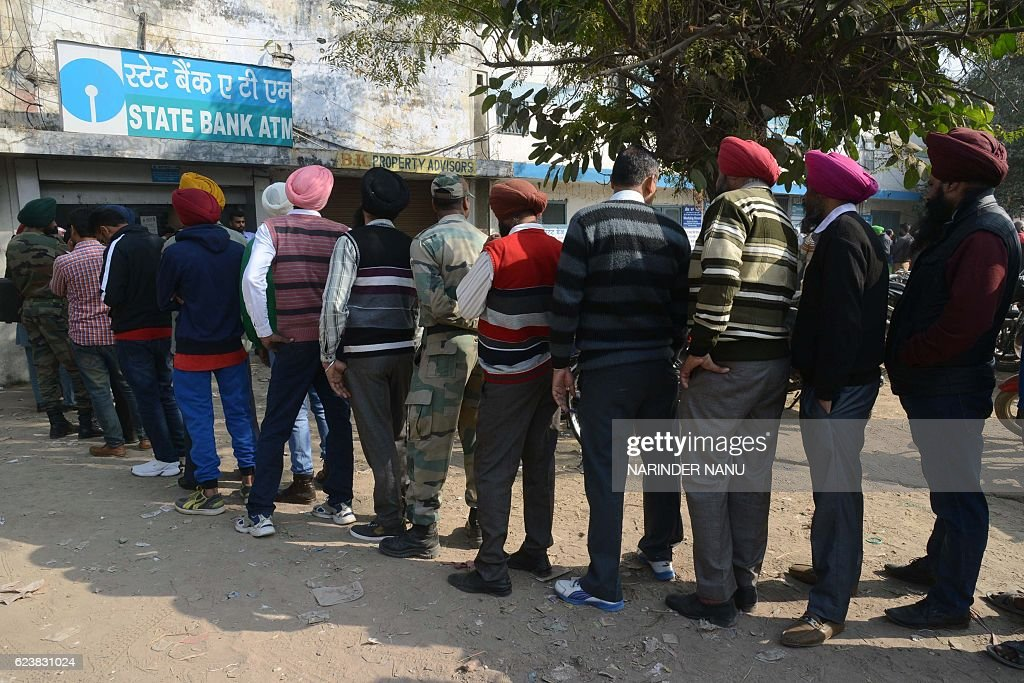 Indian people stand in a queue to withdraw money from an ATM in Amritsar on November 17 2016 Long queues formed outside banks in India since the...