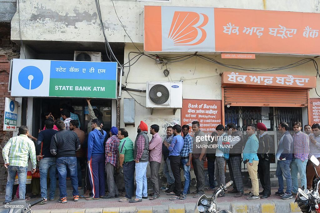 Indian people stand in a queue to withdraw money from an ATM in Amritsar on November 18 2016 India`s government asked its citizens to put up with...
