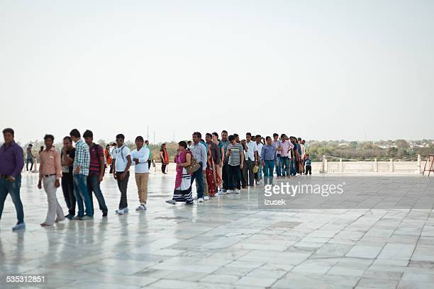 indian people standing in a row to visit taj mahal - izusek stock pictures, royalty-free photos & images