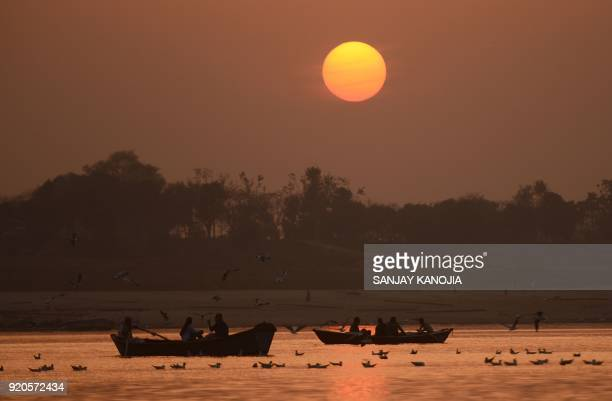 TOPSHOT Indian people take an evening boat ride during sunset at the Sangam the confluence of the Yamuna and Ganges river in Allahabad on February 19...