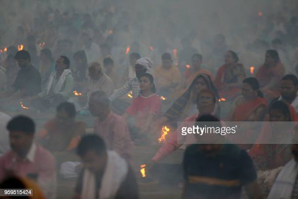 Indian people take part in a group 'Agnihotra' organised by Madhav Sansthan in Bhopal on 17 May 2018 Agnihotra is a fire a ritual lit using cow dung...