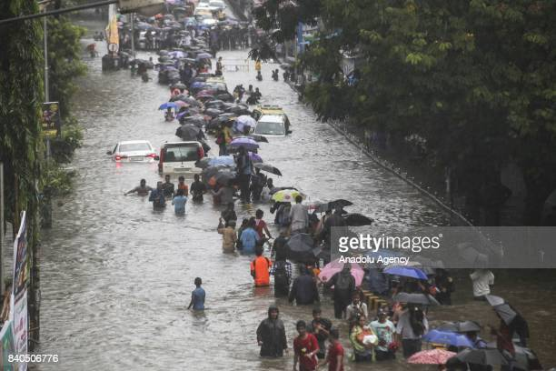 Indian people wade along a flooded street as car get stuck during heavy rain in Mumbai on August 29, 2017. Heavy rain brought India's financial...