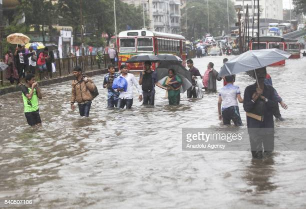 Indian people wade along a flooded street during heavy rain in Mumbai India on August 29 2017 Heavy rain brought India's financial capital Mumbai to...
