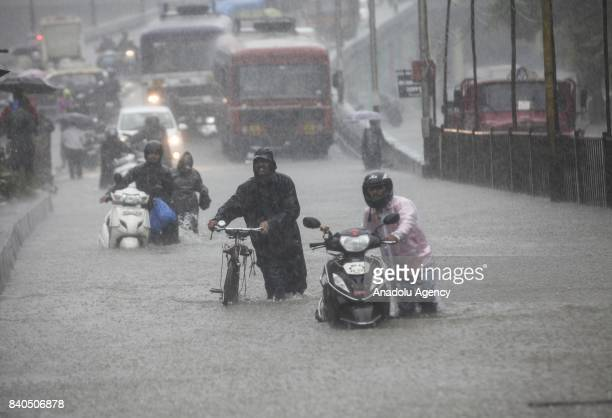 Indian people wade along a flooded street with their motorcycles during heavy rain in Mumbai, India on August 29, 2017. Heavy rain brought India's...