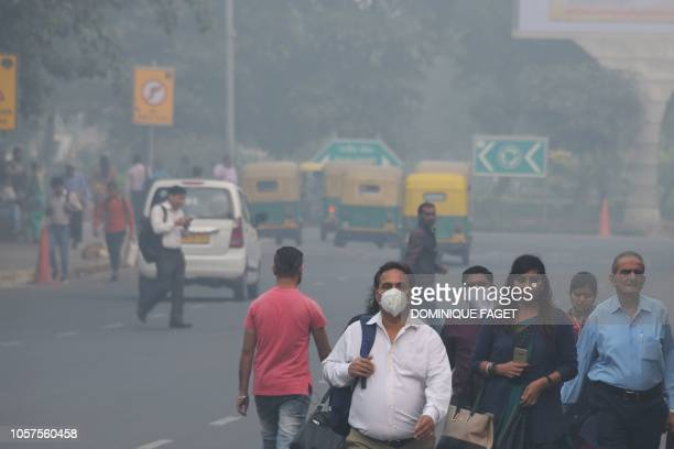 Indian people walk along a street as heavy smogs covers New Delhi on November 5 2018 Smog levels spike during winter in Delhi when air quality often...