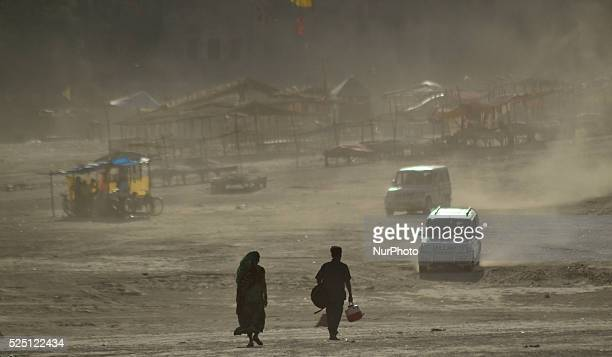 Indian people walk as they return after taking a holy dip at sangamconfluence of RIver GangaYamuna and mythical Saraswatiduring dust storm in...