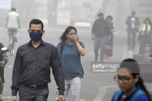 Indian people walk on a street as heavy smogs covers New Delhi on November 8 2017 Delhi shut all primary schools on November 8 as pollution levels...