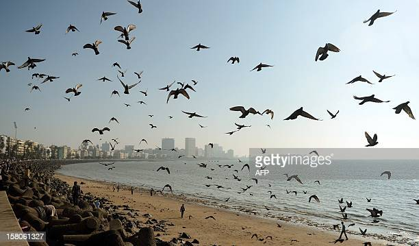 Indian people walk on Chowpatty beach as the skyline is seen in the distance in Mumbai on December 10 2012 India is part of a global trend that is...
