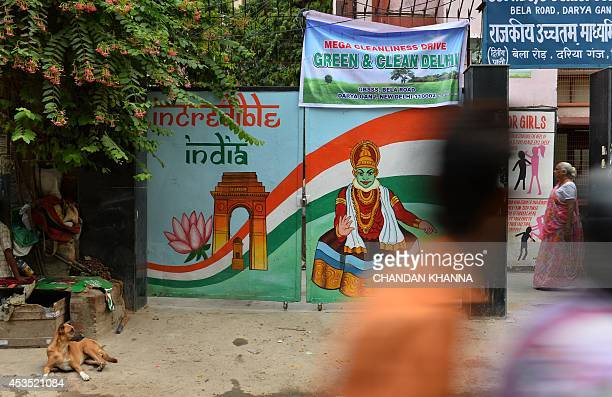 Indian people walk past a poster of Hindu monkey god Hanuman decked with the colors of the national flag outside a school in New Delhi on August 12...