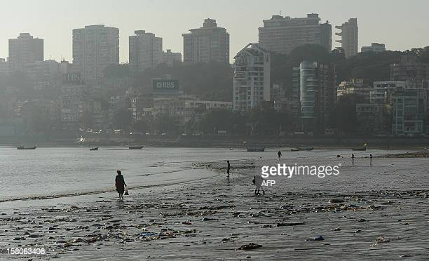Indian people walk through plastic garbage on Chowpatty beach in Mumbai on December 10 2012 Though the government has imposed a blanket ban on the...