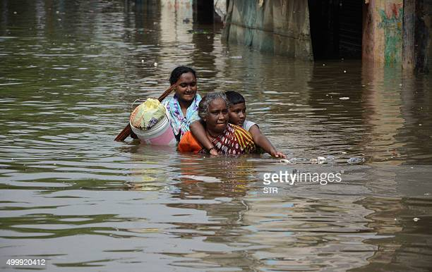 Indian people walk through through floodwaters on a street in Chennai on December 4 2015 Thousands of rescuers are racing to evacuate victims of the...