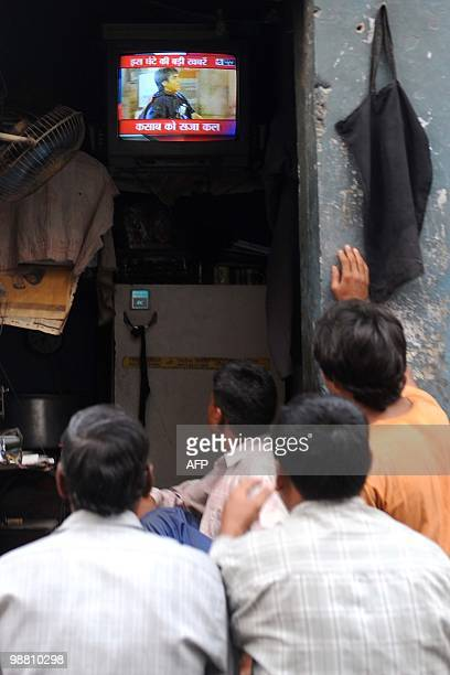 Indian people watch a television showing the Indian court verdict against alleged surviving gunman of the Mumbai massacre Mohammed Ajmal Amir Kasab...