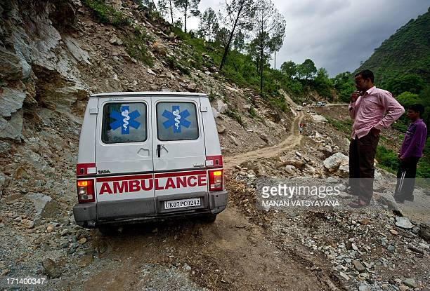 Indian people watch as an ambulance makes its way along a damaged section of the road caused by overnight rains in Gauchar on June 24 2013 Indian...