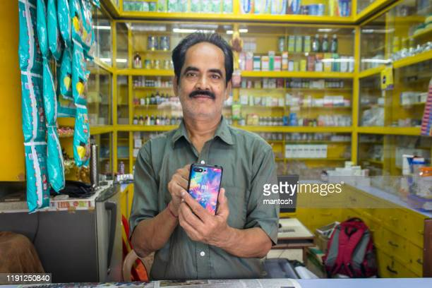 indian pharmacist using smart phone app. - indian culture stock pictures, royalty-free photos & images