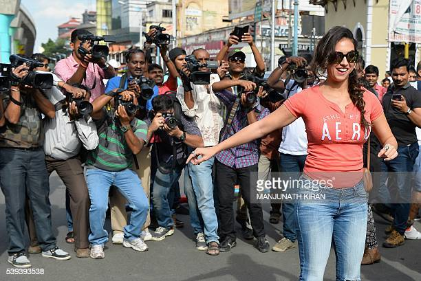 Indian photographers and cameramen jostle to take photographs of US dancer and Bollywood actress Lauren Gottlieb on a hover board in Bangalore on...
