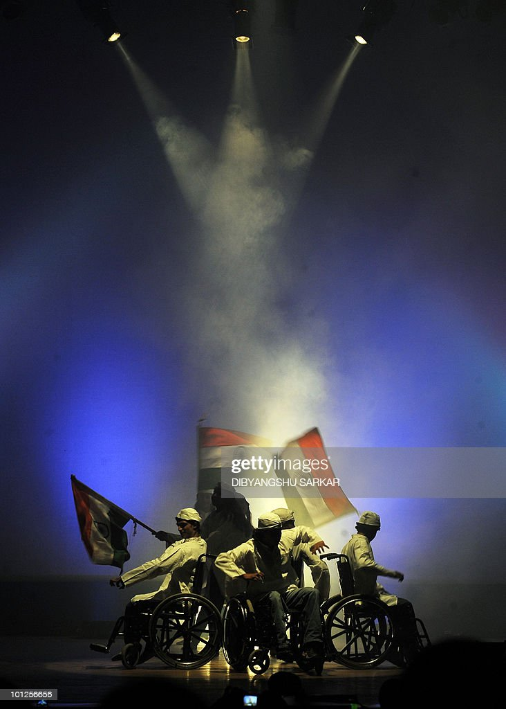 Indian physically challenged artists in wheelchairs dance and hold national flags during a performance of the national anthem Vande Mataram at a function in Bangalore on May 28, 2010. NGO Abilities Unlimited works with artists who suffer conditions such as polio, dyslexia, cerebral palsy and autism and is the first professional dance�theater troupe in India to educate and employ people with disabilities through choreographed works and public performances that integrate the arts with career opportunities and training. AFP PHOTO/Dibyangshu Sarkar