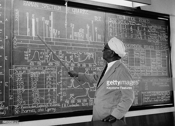 Indian physicist Sir C V Raman pointing to information on a large blackboard as he gives a lecture, August 5th 1958.