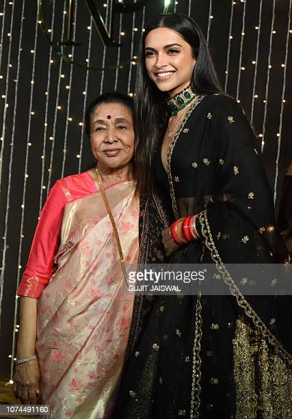Indian playback singer Asha Bhosle and Bollywood actress Deepika Padukone pose for a picture during the wedding reception party of actress Priyanka...