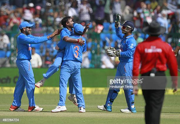Indian player Amit Mishra celebrates with team members after the dismissal of South Africa`s Hashim Amla during the first One Day International match...