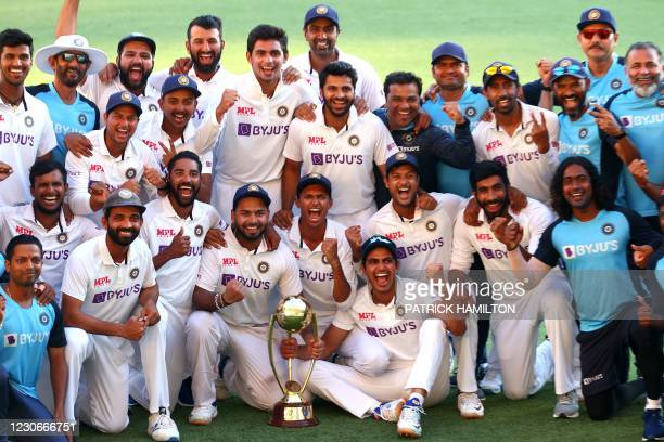 Indian players and officials celebrate with the winning trophy at the end of the fourth cricket Test match between Australia and India at The Gabba...