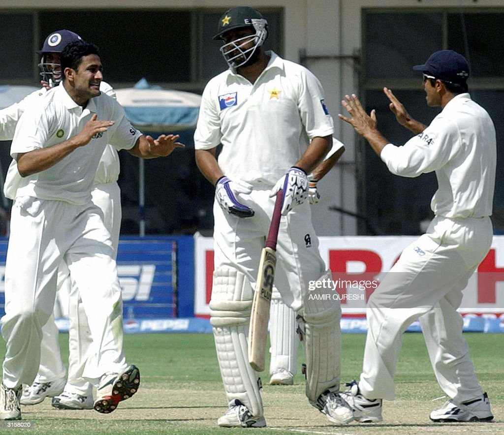 Indian players Rahul Dravid (R) and spin bolwer Anil Kumble (L) celebrate as dismissal of Pakistani batsman Inzamam-ul-Haq (C) during the third days play of the first Test match between Pakistan and India in Multan, 30 March 2004. Chasing India's first inning's score of 675 runs, Pakistan made 252 for the loss of four wickets at the tea break. AFP PHOTO /Aamir QURESHI